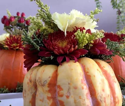 a decorative pumpkin and floral centrepiece